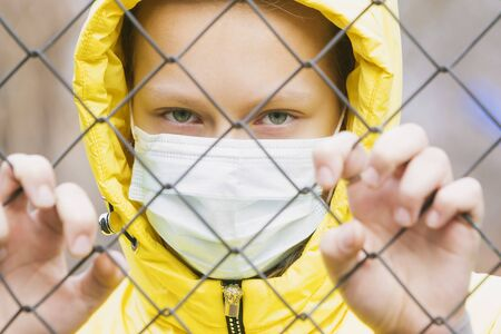 The quarantined girl in the medical mask looks through the metal mesh of the fence. Stockfoto