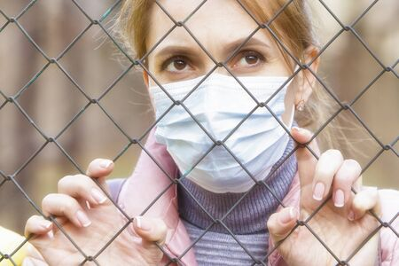 The quarantined woman in the medical mask looks through the metal mesh of the fence.