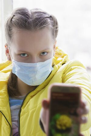 Girl at home with phone near window in isolation in medical mask.