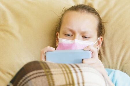 A girl in a medical mask lies at home with a gadget in her hands. Stockfoto