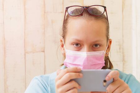 Girl in medical mask at home with a phone in quarantine isolation.