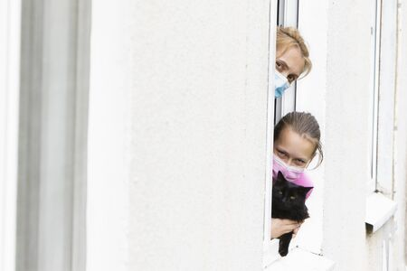 Mom and daughter in medical masks, together with their pet, look out of the window during a pandemic. Stockfoto