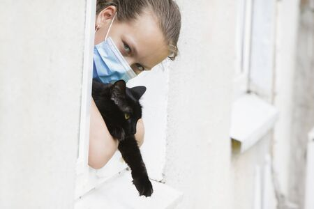Girl child in a medical mask with a pet looks out of the window during a pandemic.
