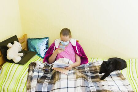 Schoolgirl wearing medical mask with her pet is engaged at home during isolation.