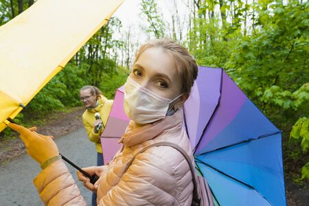 Mom in a medical mask with colored umbrellas walk with her daughter in the forest.