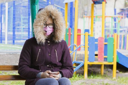 Girl child in a medical mask and with a phone sits on a childrens playground.