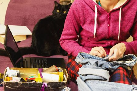 A woman with a sewing needle in her hands performs two tasks at once, home and work online with a cat. Stockfoto