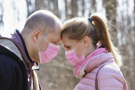 Man and woman in medical masks touch each others heads in nature during quarantine.