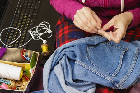 Woman sew jeans by hand, a laptop lies nearby.