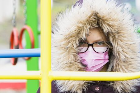 Portrait of a girl in a medical mask and glasses at the playground.