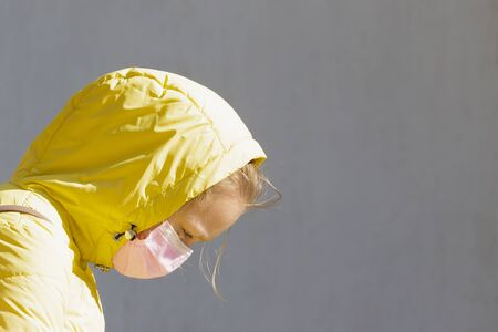 Girl in a medical mask and a yellow hood on a gray background with free space. Stockfoto
