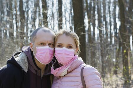 Man and woman in medical masks hug each other outdoors during quarantine, family