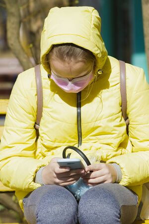 Girl in a medical mask sits in the fresh air and looks at the phone Stockfoto