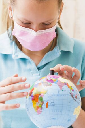Girl in a medical mask touches the globe with her hands. Stockfoto