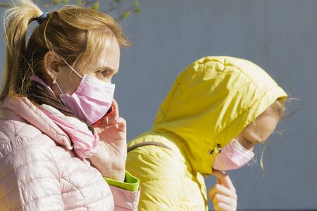 Girl with mom in medical masks sit near the house.