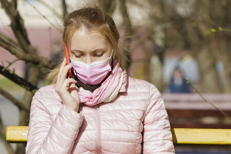 Portrait of a young woman on a bench in a medical mask talking on the phone