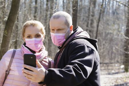Man and a woman in medical masks walk and take pictures in the forest during quarantine. Stockfoto