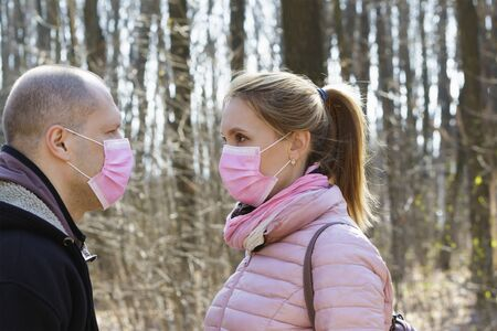 Man and woman in medical masks walk in the forest during quarantine.