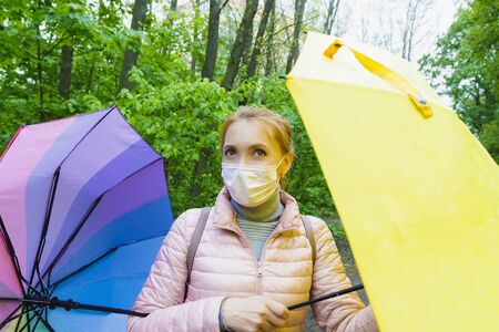 Young woman in a medical mask with colored umbrellas walks in the forest during quarantine. Stockfoto
