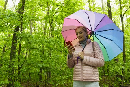 Young woman walk in the spring forest under a colorful umbrella.
