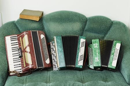 Old accordions with a book lie on a retro sofa