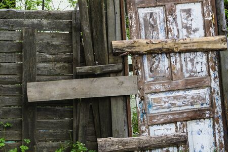 Old vintage fence with boarded up doors