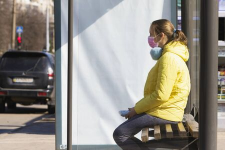 Girl in a medical mask sits near the road during quarantine