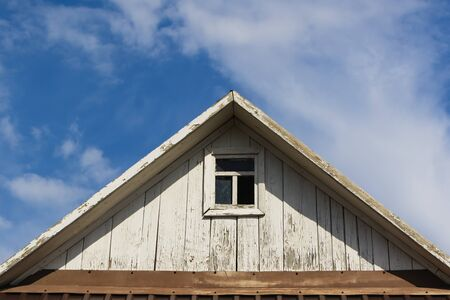 The roof of an old wooden house with a window against the sky