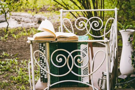 Accordion with an open book in the wind in the garden on an old vintage bed Stockfoto