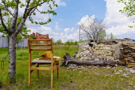 Old chair with an open book in the garden. Pages flip in the wind