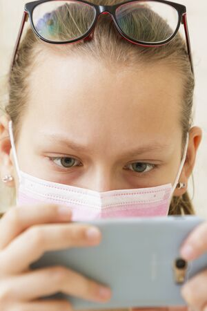Girl in a medical mask with low vision and glasses on her head looks at the phone Stockfoto