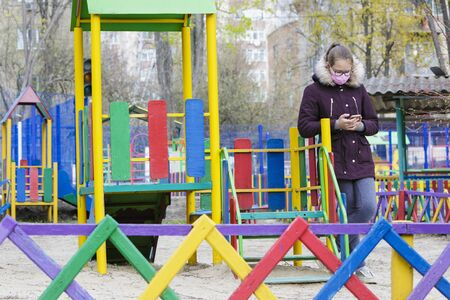 Girl in medical mask and with phone on colored playground during quarantine