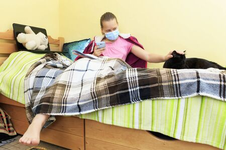Schoolgirl wearing medical mask with her pet is engaged at home during isolation