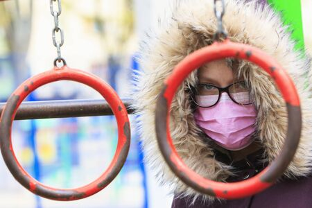 Portrait of a girl in a medical mask and glasses on a children 's sports playground