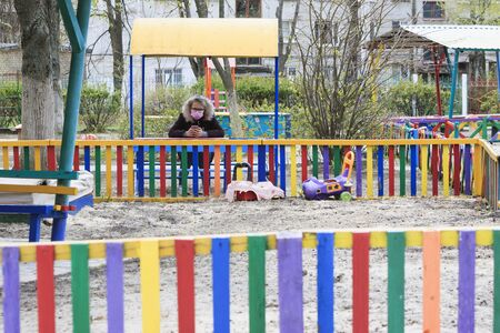 Child in medical mask and with phone on colored playground during quarantine