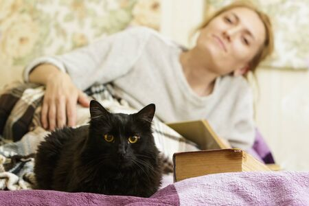Young woman reading a book in bed with her pet