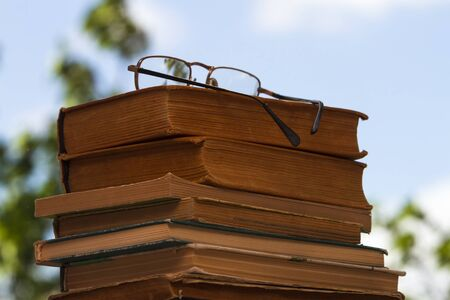 Stack of old books with glasses