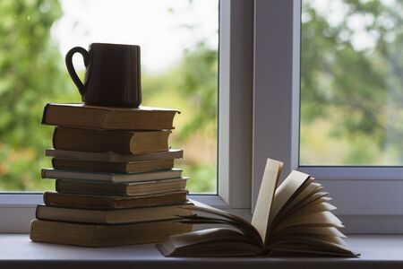 Pile of old books lies on a windowsill Stockfoto