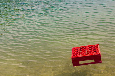 Plastik: Red beer crate swims alone through a sea Stock Photo