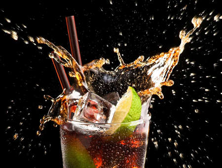 Ice cube and lime splashing cola in glass ,cuba libre, black background, closeup