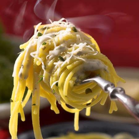 spaghetti saus: verse hete spaghetti met kaas op vork met damp, close-up, vierkant formaat