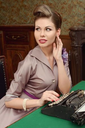 Pin Up beautiful young woman in vintage interior prints on an old typewriter photo