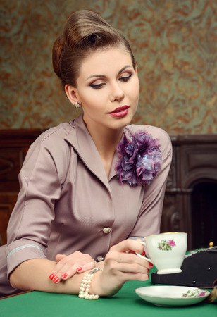 Pin Up beautiful young woman in vintage interior drinking tea photo