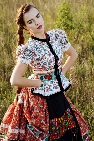 Young peasant woman, dressed in Hungarian national costume, posing over nature background photo