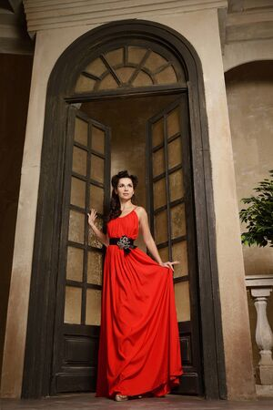 feminity: Young beautiful woman in red dress at the arc