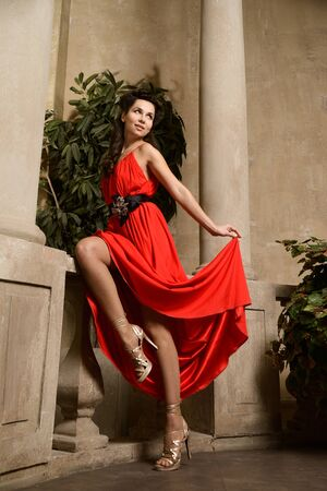 stylishness: Young beautiful woman in red dress at the arc