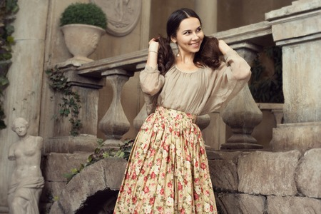 impish: Young beautiful woman in flower skirt at Italian pation