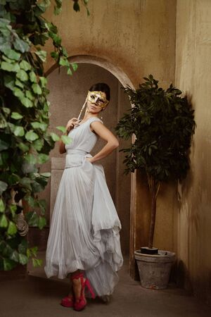 studioshoot: Young beautiful woman with Venice mask in patio