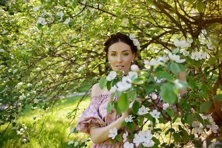 feminity: Young beautiful woman in pink dress at the garden Stock Photo