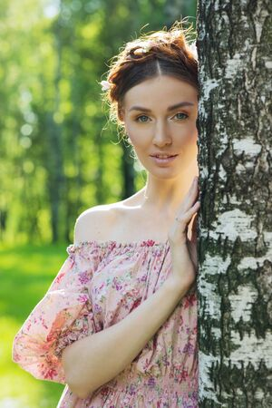 stylishness: Young beautiful woman in pink dress at the garden Stock Photo